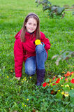 Girl kid posing with a flower in a meadow Stock Image