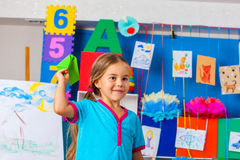 Girl kids holding origami airplane in kindergarten . Royalty Free Stock Photo
