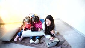 Girl and kids using new technologies like tablet laptop and smart phone on chrismas background. One young female and two kids girls using gadgets like  tablet stock footage