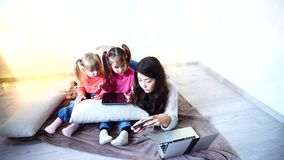 Girl and kids using new technologies like tablet laptop and smart phone on chrismas background. One young female and two kids girls using gadgets like  tablet stock video