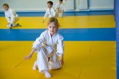 Girl in Kimono. Girl in white kimono sits on the mat Stock Image