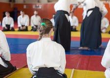 A girl in kimono and hakama sitting on tatami on martial arts seminar Royalty Free Stock Photos