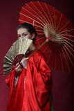 Girl in a kimono with an umbrella and a fun Royalty Free Stock Images