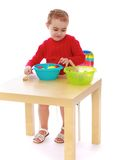 Girl in kindergarten playing artificial fruit Stock Images