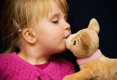 Girl kiss toy bear stock image