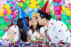Girl kissed by her parents at birthday party Royalty Free Stock Photography