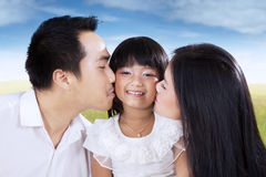 Girl kissed by her parents on meadow Royalty Free Stock Image
