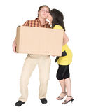 Girl kisses the guy holding a box Royalty Free Stock Photos