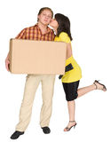Girl kisses the guy holding a box. The girl kisses the guy holding a box Stock Image