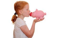 Girl kisses a piggy bank Stock Image