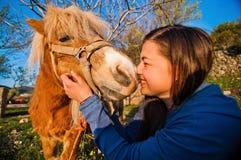 Girl kisses the pony. Stock Photos