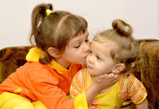 The girl kisses the younger little sister. Portrait.  Royalty Free Stock Photos