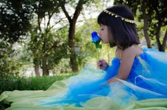Girl kissin blue rose. Little girl kissin a blue rose at the park Royalty Free Stock Photos