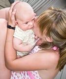 Girl Kissing a Baby stock photos