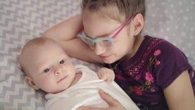 Girl kissing baby. Older sister kiss newborn brother. Sister love concept. Girl kissing baby lying on sofa. Older sister kiss newborn brother. Beautiful girl stock footage
