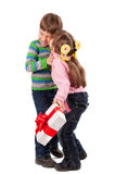 Girl kissing a boy with gift box Stock Images