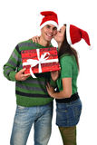 Girl kissing boyfriend hold present in Santa hat Royalty Free Stock Image