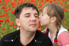 Girl kissing on the cheek father.  Royalty Free Stock Image