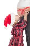 Girl kissing christmas gift - pregnant mother Stock Image