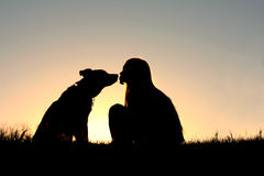 Girl Kissing Dog Silhouette. A silhouette of a woman with long blonde is sitting outside in the grass, kissing her large German Shepherd Mix dog at sunset Royalty Free Stock Images