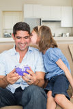 Girl kissing father holding gift box on sofa Stock Photo