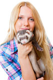 Girl kissing a ferret Stock Images