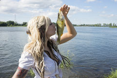 Girl kissing fish. Picture of beautiful blond girl kissing a fish Royalty Free Stock Photos