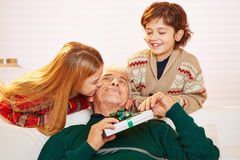 Girl kissing grandfather with gift at christmas Royalty Free Stock Photography