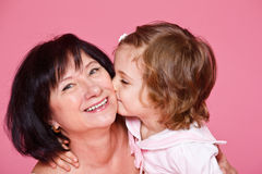 Girl kissing grandmother Stock Photos