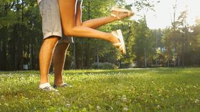 Girl kissing a guy. Close-up legs of guy and girl. Lovers embrace. Love story in the park stock video footage