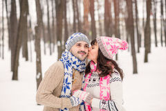 Girl kissing her boyfriend on the cheek in winter outdoors. Wearing cozy warm clothes, knitted  hat and gloves . Winter dating con Stock Images