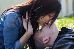 Girl kissing her boyfriend, outdoors Royalty Free Stock Photography