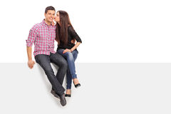 Girl kissing her boyfriend seated on a panel Stock Photography