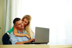 Girl kissing her boyfriend while he using laptop Royalty Free Stock Images