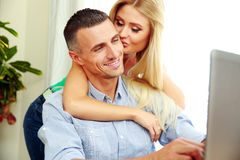 Girl kissing her boyfriend while he using laptop Stock Photography