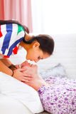 Girl kissing her boyfriend who laying on sofa Royalty Free Stock Photos