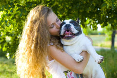 Girl kissing her dog Stock Image