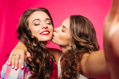 Girl kissing her friend while making selfie. Stock Images