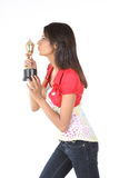 Girl kissing her gold trophy Royalty Free Stock Images