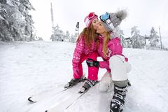 Kiss to mother before descend with skis. Girl kissing her mother before descend with skis Royalty Free Stock Photo