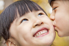 A girl kissing her older sister Stock Photo
