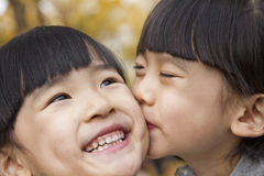 A girl kissing her older sister, smiling royalty free stock images