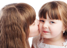Girl kissing her sister Stock Photo