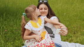 Girl kissing her sister, and they do selfie on grass. Two girls doing selfi in grass stock footage
