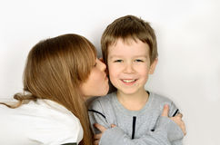 Girl kissing little cheerful boy on light gray background. he fo Royalty Free Stock Photo