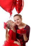 Girl kissing mother and giving gift box with balloons Stock Image