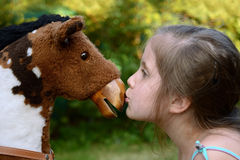Girl kissing a rocking horse. Royalty Free Stock Images