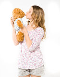 Girl kissing a teddy bear Stock Photos