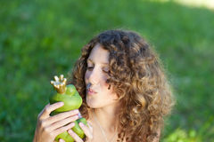 Girl Kissing Toy Frog In Park Stock Images
