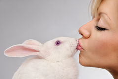 Girl kissing white rabbit Stock Photos